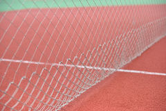 Detail of net tennis on field made from red granule rubbe. Selec Stock Image