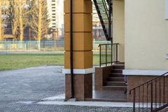 Detail of new kindergarten or school building corner with supporting column, staircase, metal fence and handrails on sunny. Outdoors background royalty free stock images