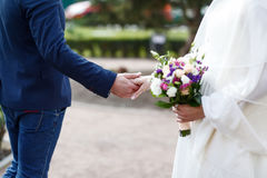 Detail of newlyweds, bride and groom, holding hands and flower bouquet, side view. Stock Images