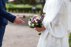 Detail of newlyweds, bride and groom, holding hands and flower bouquet, side view. Stock Photos