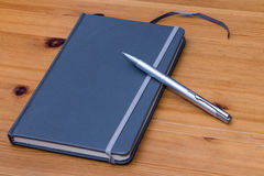 Detail of a notebook and pen on wooden table Stock Images