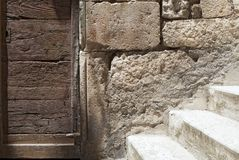 Detail of old, abandoned stone built facade with door and stairs. Decaying wooden door on stone built facade and stairway in aged mediterranean town stock image