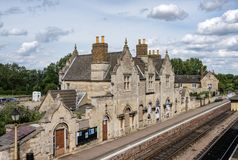 Detail of an old and abanonded Train Station seen together with its platform and railway tracks. Stock Photos