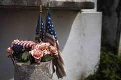 Detail of old American flags and flowers placed in a tomb in a New Orleans cemetery, in Louisiana. USA Royalty Free Stock Photos