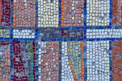 Detail of an old antique mosaic. With colored glass on the wall of an old building, built in the USSR. a typical plot of street art of the USSR period. Mass Royalty Free Stock Photos