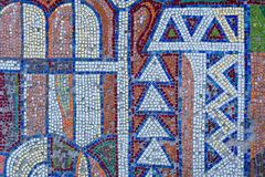 Detail of an old antique mosaic. With colored glass on the wall of an old building, built in the USSR. a typical plot of street art of the USSR period. Mass Stock Image