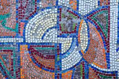 Detail of an old antique mosaic. With colored glass on the wall of an old building, built in the USSR. a typical plot of street art of the USSR period. Mass Royalty Free Stock Photo
