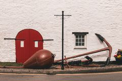 Detail of an old barn red door with black metal hinges against a white wall and a huge anchor outside. On the street Royalty Free Stock Photos