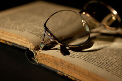 Detail of old book with glasses Royalty Free Stock Photo