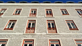 Detail of an old building with portuguese tiles and red and whit Royalty Free Stock Photo