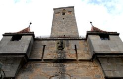Detail of an old building with stone mask and old tower in the town of Rothenburg in Germany Stock Image