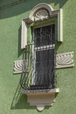 Detail of an old building. And a window with metal grille Stock Photo