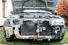 Deatil of the front of the car wreck. A detail of the old car wreck. The front of the car is visible, some parts are missing. The engine and radiator are without Stock Images