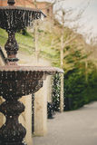 Detail of an old classic style fountain with flowing water. Outdoor garden fountain. Stock Photos