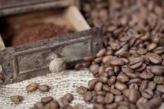 Detail of an old coffee grinder with coffee beans. Antique coffee grinder filled with coffee beans and ground coffee - selective focus Royalty Free Stock Images