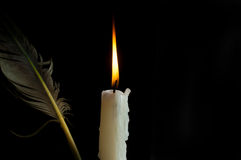 Detail of old feather and candle isolated on black Stock Photos