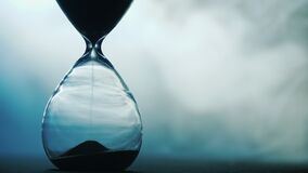 Detail of old hourglass, grains of sand fall down measuring time