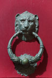 Detail of an old iron handle in the shape of lion. Red Royalty Free Stock Photo