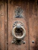 Detail an old knocker with a round shape. Detail an old round knocker hanging from a wooden door royalty free stock image