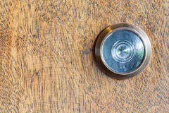 Detail of old lens peephole on wooden door background. Royalty Free Stock Images