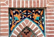 Detail of old mosaic wall with traditional georgian floral pattern. Of yellow and blue colors in brick frame royalty free stock image