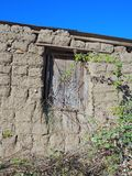 Mud Brick Hut. Detail of an old mud brick shed or hut, with a closed wooden window, Greece. The mud bricks have been heavily eroded by wind and rain Royalty Free Stock Photos