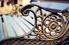 Detail of old park bench with ornaments, bokeh background Royalty Free Stock Images
