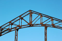 Detail of old rusty metal bridge against blue sky background Royalty Free Stock Photo