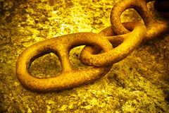 Detail of an old rusty metal chain anchored to a concrete block Stock Images