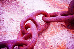 Detail of an old rusty metal chain anchored to a concrete block Stock Photo