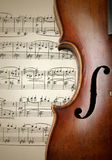 Detail of old scratched violin on music sheet Royalty Free Stock Photography