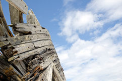 Detail of an old shipwreck. With clouds in a blue sky Stock Photography