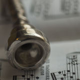 Detail of an old Silver Trumpet mouthpiece on sheet music book. A silver trumpet mouthpiece on sheet music book Royalty Free Stock Photos
