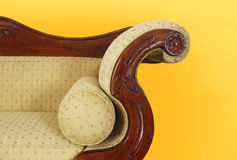 Detail of an old sofa on a yellow background Stock Photo
