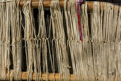 Detail of old traditional weaving loom and shuttle on the warp. Weaving loom for homemade on vintage background. Stock Photos
