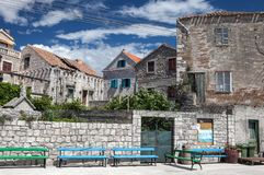 Detail of old village Šepurine on Prvić island. Colorful benches in the front of old, stone built houses of Šepurine village and blue, cloudy sky in stock images