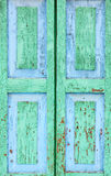 Detail of an old window. Peeling paint green and blue color on the wooden shutters. Royalty Free Stock Photos