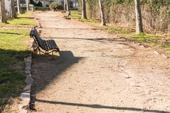 An old wooden bench in the only shadow a park in a peripheral area of Caceres, Extremadura, Spain. stock photography