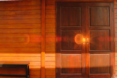Detail of Old wooden door front view with lighting flare effect. Royalty Free Stock Photo
