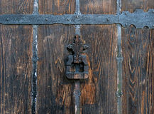 Detail of an old wooden door with an iron knocker. Showing the age and patina of the iron fittings, and the weathered wood Stock Image