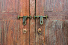 Detail of an old wooden door with two rusty copper latches Royalty Free Stock Photos