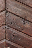 Detail of an old wooden doorway with keyholes and  Royalty Free Stock Photography