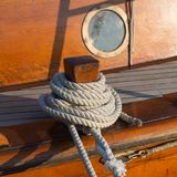 Detail of an old wooden sailing ship with rope and porthole. The detail of an old wooden sailing ship with rope and porthole Stock Image