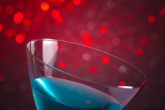 Detail of one glass blue cocktail on red tint light background Royalty Free Stock Images