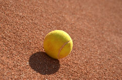 Detail of one isolated tennis ball on the clay tennis field Royalty Free Stock Photos