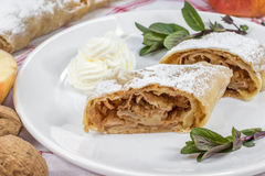 Detail on a One Slice Homemade Apple Strudel on a Plate with Whipped Cream and Mint royalty free stock photography