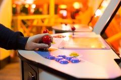 Detail op een hand die rode bedieningshendels en oude arcade houden Stock Foto's