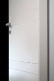 Detail open white door. Open white door on black background stock photos