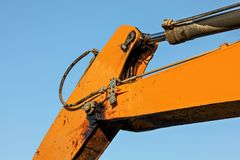 Detail on orange arm of excavator machine, hydraulic piston mechanism and joint dirty from black oil visible. Afternoon blue sky stock photography