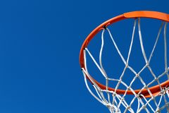 Detail of an orange basketball rim hoop and white net against blue sky Royalty Free Stock Images